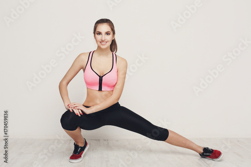 Wall mural Fitness woman at stretching training indoors