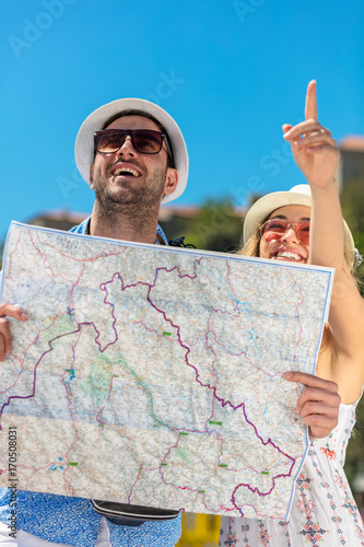 Multiethnic traveler couple using generic local map together on sunny day.