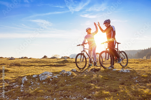 happy couple goes on a mountain asphalt road in the woods on bikes with helmets giving each other a high five - 170509838