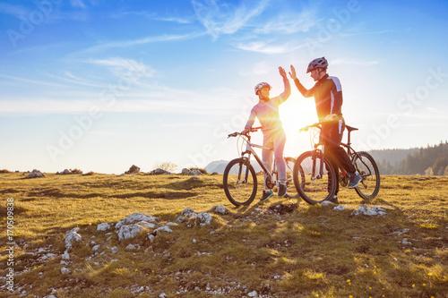 szczęśliwa para idzie na górskiej drodze asfaltowej w lesie na rowerach z kaskami dając sobie piątkę