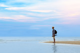 Young traveler man with backpack standing at seaside and looking to the ocean