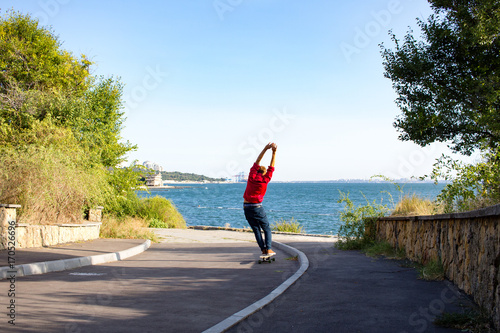 Fotobehang Skateboard stylish skater in red shirt and blue jeans ride downhill on longboard, summer active picture