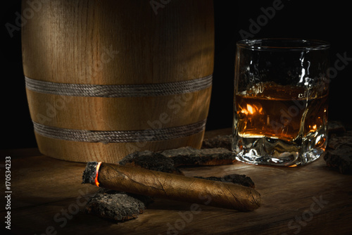 Old oak barrel, havana cigar and whiskey in glass. still life of Old aged whiskey
