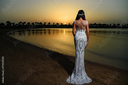 Woman in white dress in sunset beach
