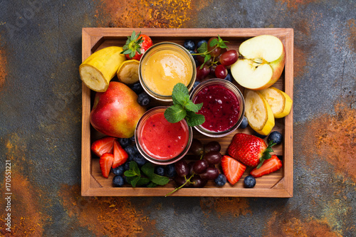 Poster Assortment of bright fruit and berry smoothies in a wooden box