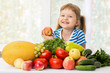 Happy little girl and a lot of fruit and vegetables. - 170554291