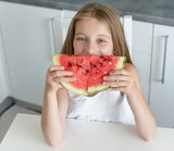 cute little girl eats a watermelon in the kitchen