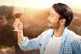 Composite image of man looking at glass of red wine - 170575065