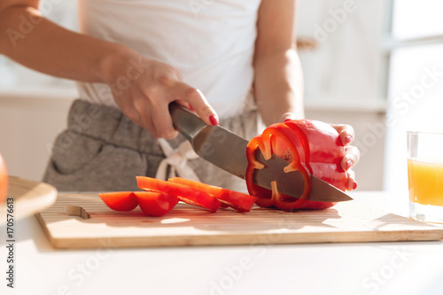 Close up portrait of young woman slicing capsicum - 170576613