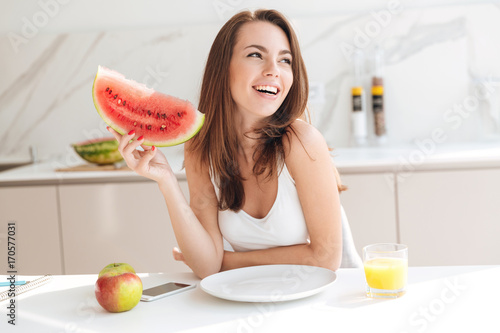 Happy smiling girl holding slice of a watermelon
