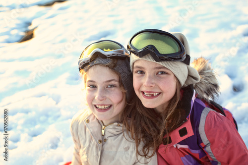 Young smiling girls play on a winter sunny day