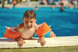 Smiling Caucasian boy getting out from the swimming pool through its side. - 170585622