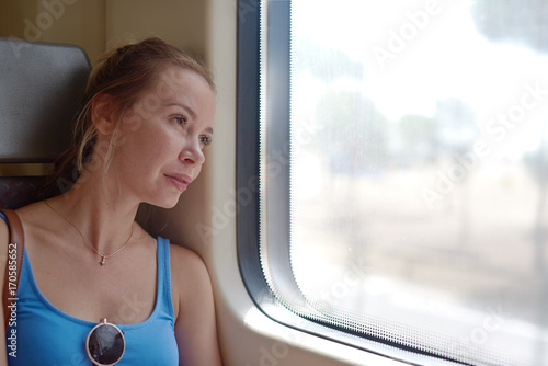 Young attractive woman in sunglasses looking into the window while travelling by train.