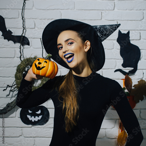 Halloween girl smiling in witch hat and black bodysuit
