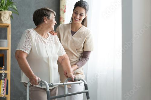 Nurse helping senior to walk