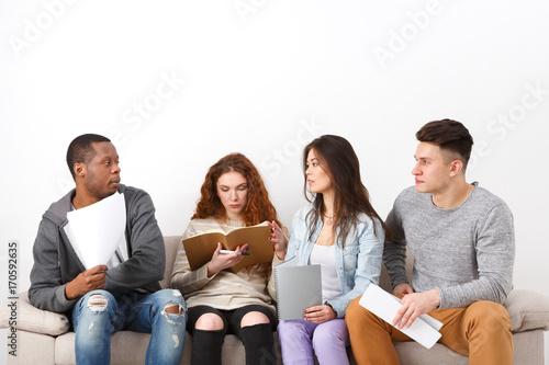 Diverse young students preparing for exam at home