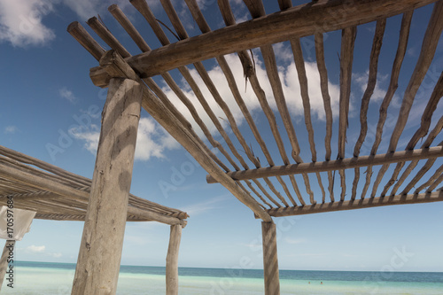 Pérgola en la playa en un día soleado Poster