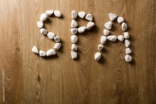 Word SPA written with white pebble letters on wooden floor
