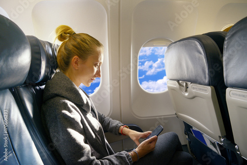 Woman messaging in airplane Poster