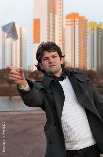 Paper airplane launching in park, free space, Man in grey coat and white sweater holding handmade paper airplane in hand on high-rise building background. Open-air game, rest, leisure, pastime concept