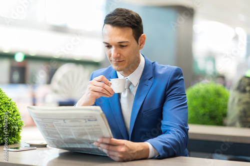 Young businessman having a coffee while reading a newspaper