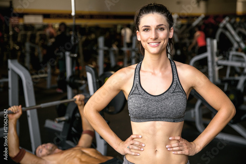 Wall mural Commercial type fitness model with perfect smile, cheerful at the gym during exercise