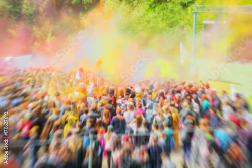 Blurred unrecognizable happy young people celebrate Holi festival