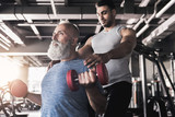 Concentrated senior male is training his biceps in gym