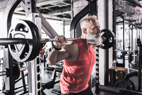 Serious mature male is having intense workout in gym