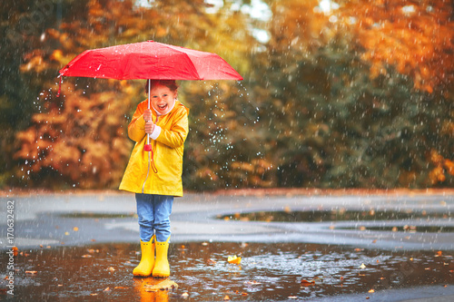 happy child girl with an umbrella and rubber boots in puddle  on autumn walk - 170632482