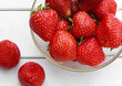 still life with ripe juicy strawberries lay in a dish and close on a white wooden table