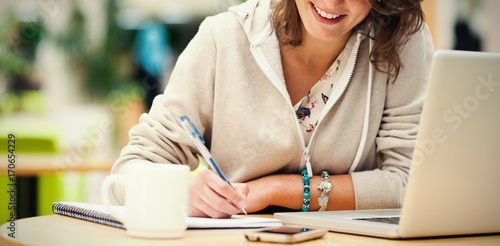 Cheerful student doing homework by laptop at cafeteria table