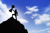Silhouette people show trophyl on top of mountain, concept as winner and success in business