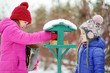 Two adorable sisters feeding birds on chilly winter day in city park. Children helping birds at winter.