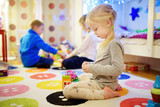 Three children playing with colorful plastic blocks at kids room. Cute girl playing at home or daycare.