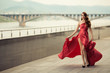 Beautiful woman in red fluttering dress. Urban background.