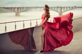 Beautiful woman in red fluttering dress. Urban background. - 170676816