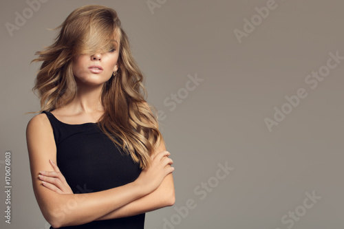 Naklejka Blond woman with long curly beautiful hair.