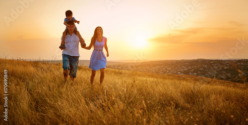 Happy family walking on field in nature at sunset.