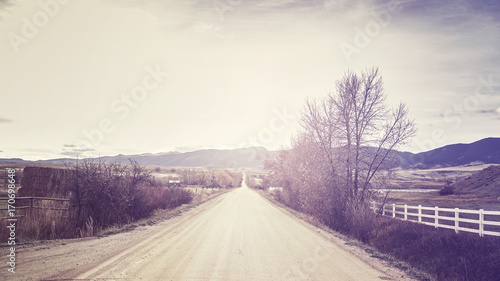 Foto op Plexiglas Beige Vintage stylized picture of a countryside road at sunset, travel concept.