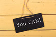 """Blackboard with text """"You can!"""" on yellow wooden background"""