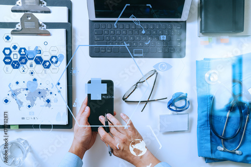 top view of smart medical doctor working with mobile phone and laptop computer and stethoscope on dark wooden desk with virtual reality icon diagram