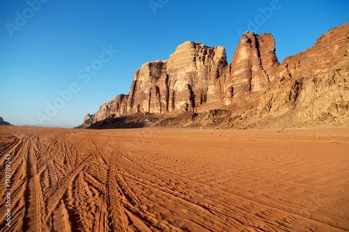 Poster Oranje eclat in the desert sand and mountain adventure destination
