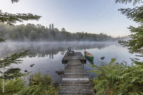 Fotobehang Canada Green canoe and dock on a misty morning - Ontario, Canada