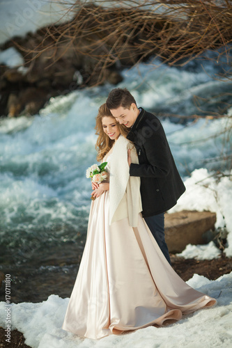 Beautiful couple in love honeymoon in the spring outdoors on a background of autumn nature and a river at sunset