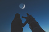 Girl looking at the stars and full Moon through a telescope. My astronomy work.