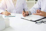 Two doctors discussing patient notes in an office pointing to a clipboard with paperwork as they make a diagnosis or decide on treatment - 170736841