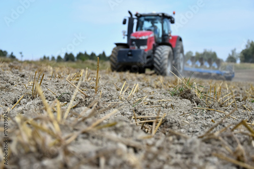 Tractor plowing a field Poster