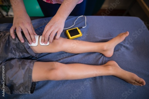 High angle view of female therapist placing electrodes on leg