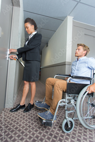 businessman in a wheelchair being assisted in a hotel